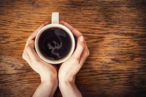manos sosteniendo taza de café