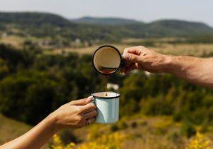 personas sirviendo café en viaje por naturaleza