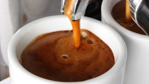 persona sirviendo café espresso