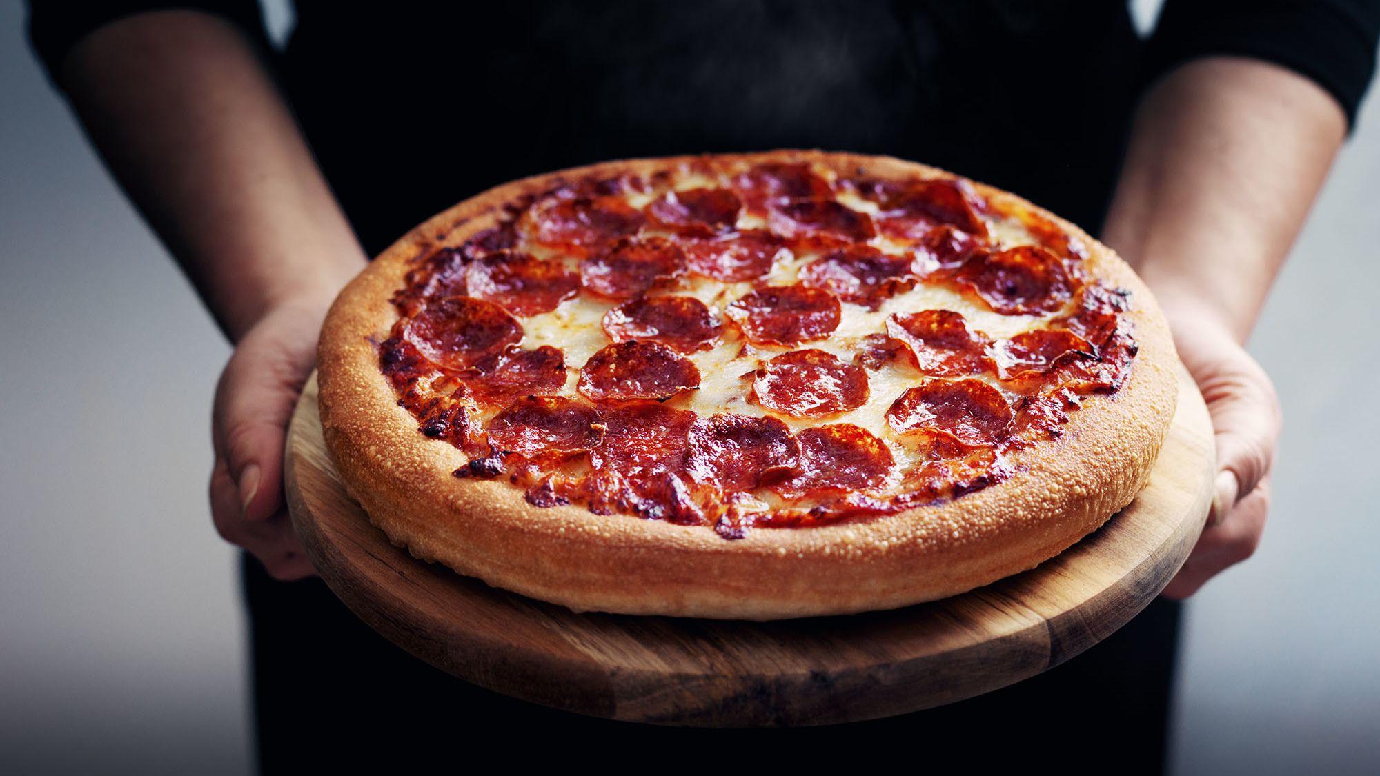 hombre agarrando una pizza de pepperoni